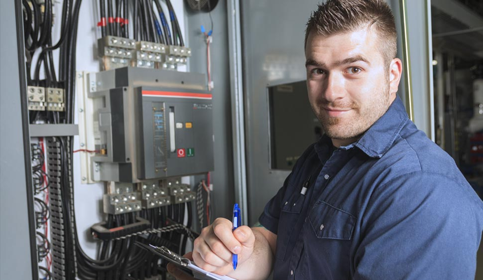service technician smiling in a work shirt in front of an electrical panel with a clip board in hand, shown from the midsection up